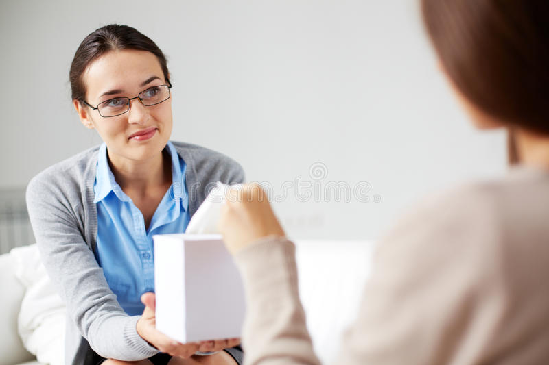 Take tissue. Careful psychiatrist giving box with paper tissues to her patient royalty free stock photography