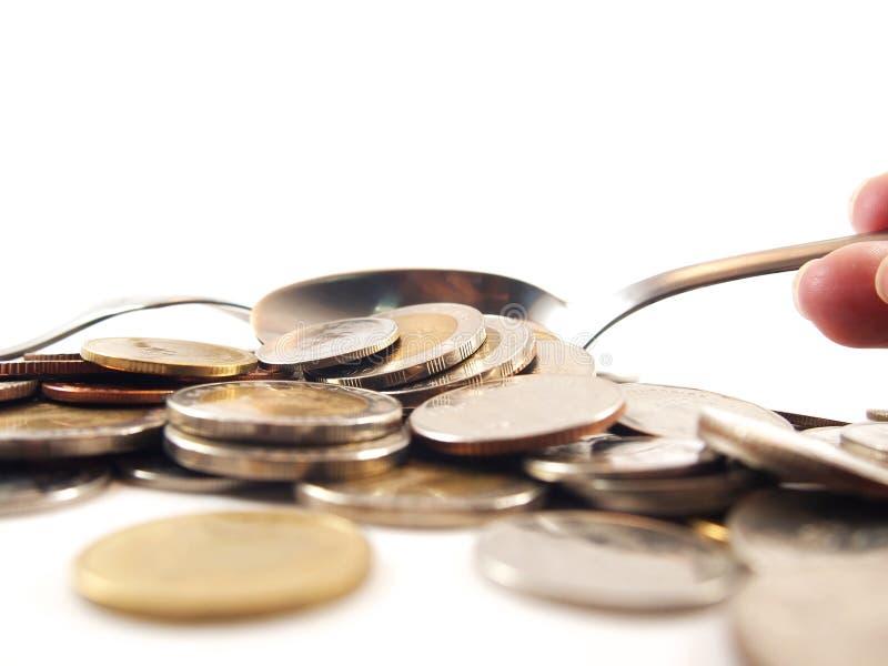 Take up coins by spoon, thai baht money stock photos