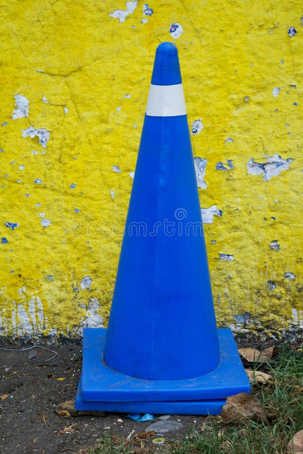 Vehicular control cone in royal blue color against a yellow wall royalty free stock photo