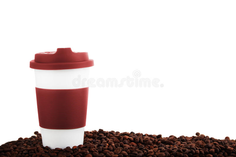 Takeaway ceramic cup and coffee beans. isolated. Takeaway red ceramic cup and scattered coffee beans isolated on white background stock photo