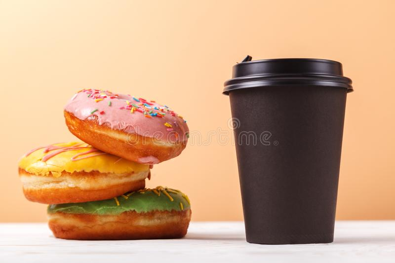 Takeaway coffee and doughnuts,a quick snack along the way. Concept of serving takeaway food for a coffee shop or bakery royalty free stock photo