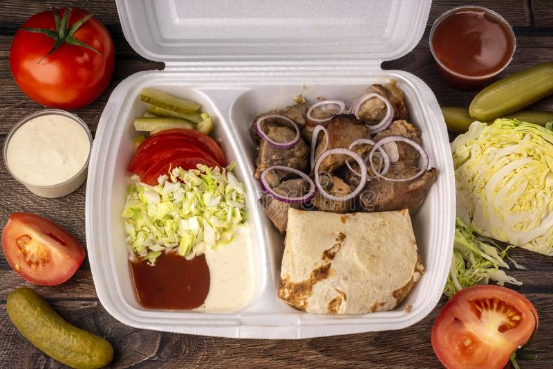 Takeaway fast food in lunch box - fresh vegetables, pita bread and pork royalty free stock image