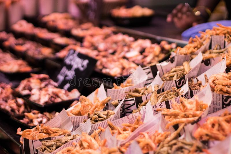 Takeaway. Fried prawns, octopus and squid in paper cones royalty free stock image