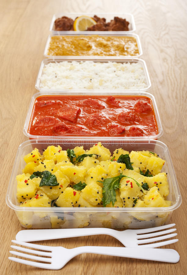 Takeaway Indian Food. A selection of Indian takeaway food in plastic containers on a wooden table. Aloo saag (potato spinach curry), chicken tikka masala,basmati royalty free stock images