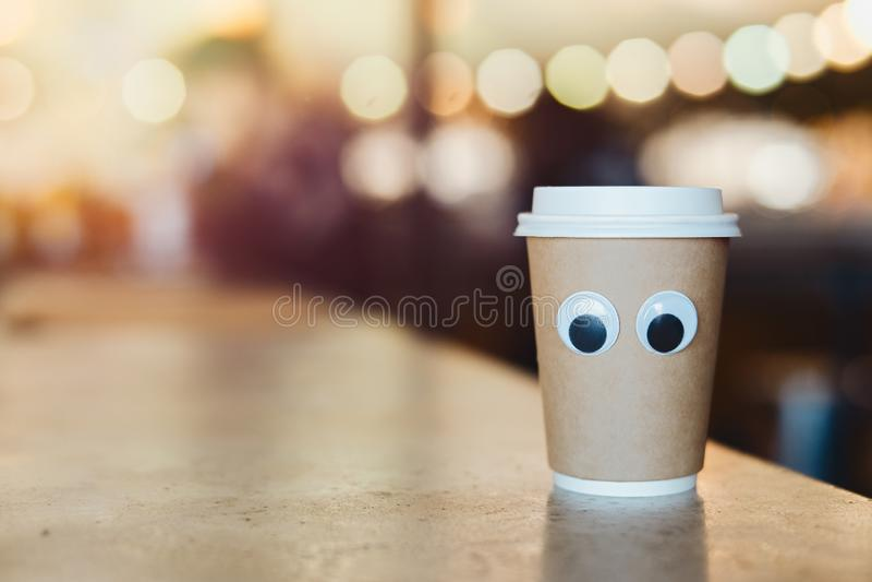 Takeaway kopp för kaffe med tecknad filmögon i kafé Begrepp av det gästfria kafét royaltyfria bilder