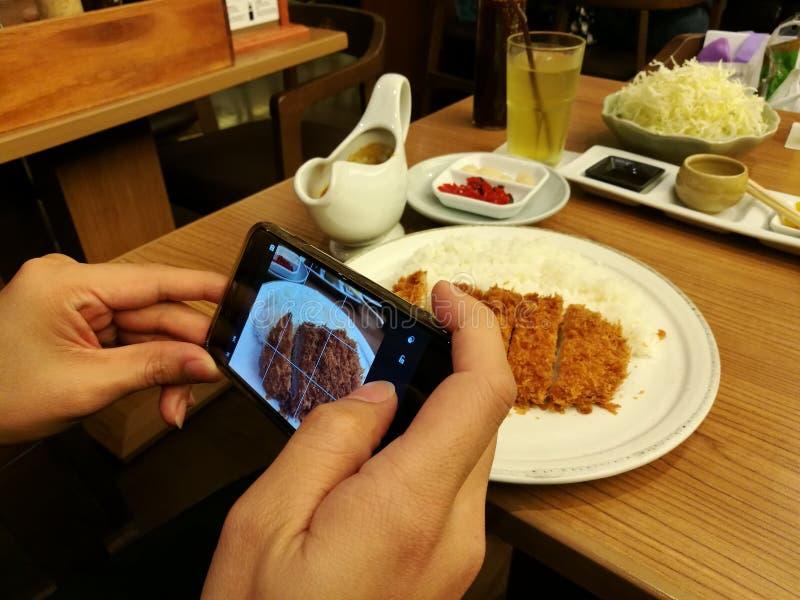 Takeing food photo before eating, Deep-fried pork slice in restaurant, Pork cutlet set, Japanese pork Tonkatsu, focus-on-foregroun stock images