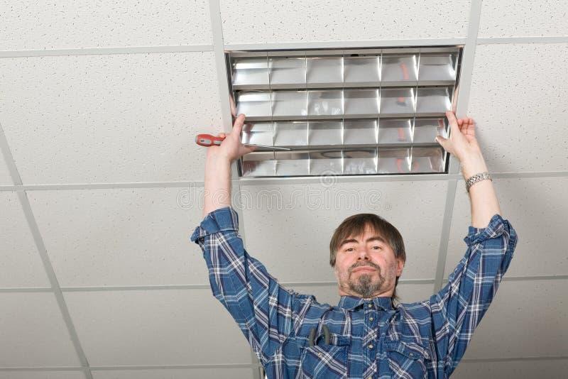 takelektrikeren installerar lighting till royaltyfri foto