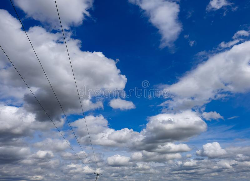 Abstract view of a leaning power utility pole seen against a dramatic summer sky. royalty free stock images