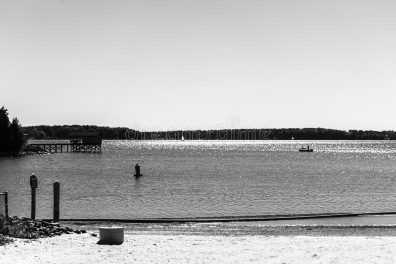 The Fishermen Tradition. Taken at Ramsey Creek Park off of Lake Norman. Black and white. Fishermen in the distance next to an old pier. Cornelius, North Carolina stock photography