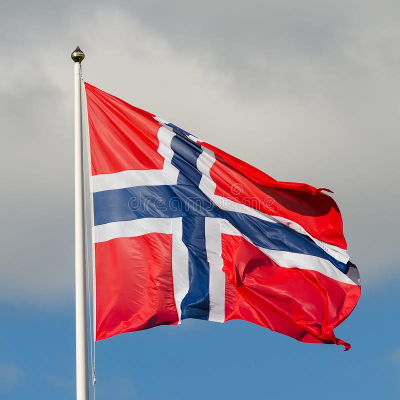 Norwegian flag on pole in windy day. Beautiful sunny day in national park south of Norway royalty free stock photos