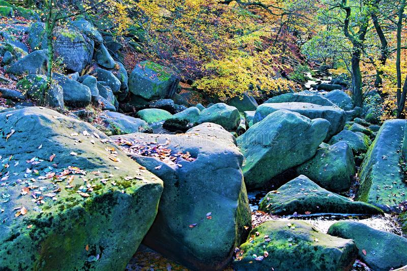 Rocks a glow, in Padley Gorge, Grindleford, East Midlands. Taken to capture the rich autumnal colours surrounding large and mossy rocks, in Padley Gorge Woods royalty free stock photo