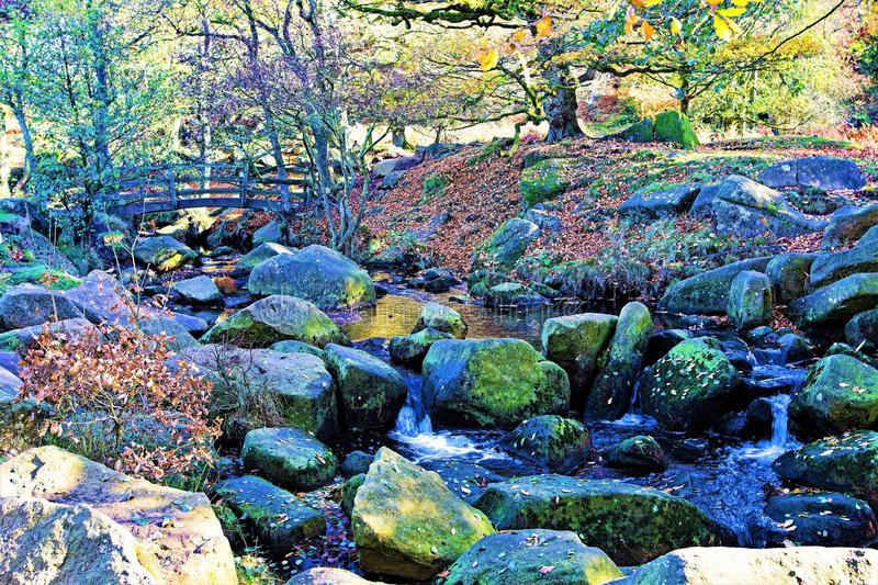 Bridge and stream, in Padley Gorge, Grindleford, East Midlands. Taken to capture the rich autumnal colours surrounding large and mossy rocks, in Padley Gorge stock photography