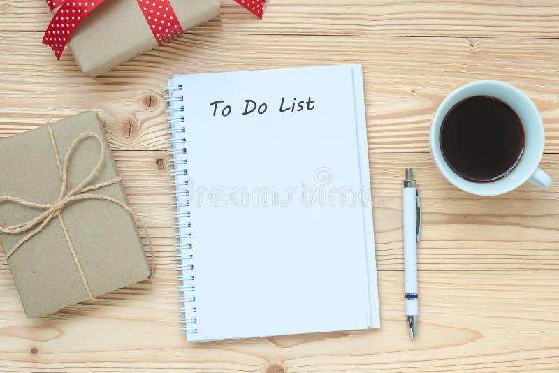 Takenlijstwoord met notitieboekje, zwarte koffiekop en pen op houten lijst, Hoogste mening en exemplaarruimte Kerstmis, Gelukkig  royalty-vrije stock foto