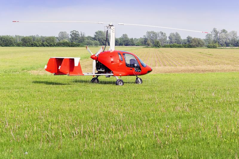 Takeoff of gyroplane. A modern small red gyroplane stands on a meadow - a horizontal photo stock images