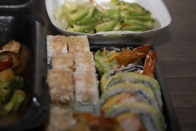 Takeout Sushi And Avocado. Sushi and avocado slices plated in takeout boxes stock images