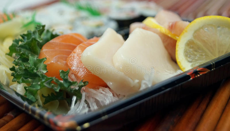 Takeout Sushi Close-Up. Fresh salmon, yellowtail snapper and white tuna sashimi in takeout trays on bamboo mat stock images