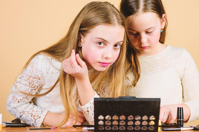 It takes makeup to look natural. Cute little girls doing makeup to find their perfect look. Adorable small children with royalty free stock images