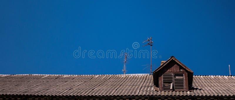 Taket av ett gammalt trähus på en bakgrund av ren blå himmel royaltyfria foton