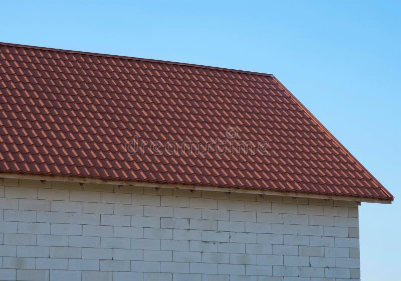 Taket av huset under röda singlar Husdetaljer mot bakgrunden av den blåa himlen royaltyfri foto