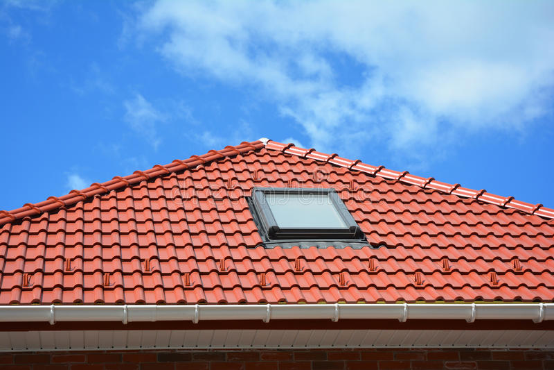 Takfönster på det röda hustaket för keramiska tegelplattor med stuprännan Takfönster, tak Windows och soltunneler Lofttakfönsterl royaltyfri fotografi