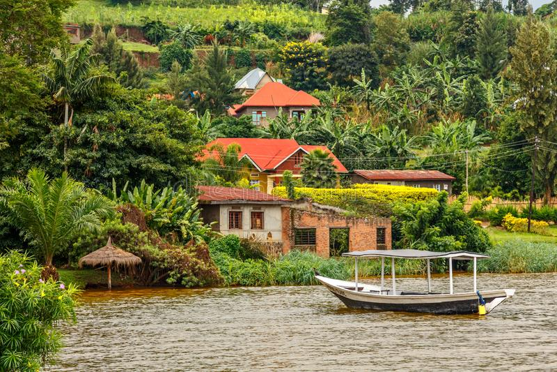 Takfartyg som ankras på kusten med den rwandan byn i bakgrunden, Kivu sjö, Rwanda royaltyfri bild
