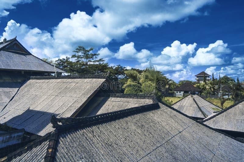 Takhus med det belade med tegel taket på blå himmel royaltyfria foton