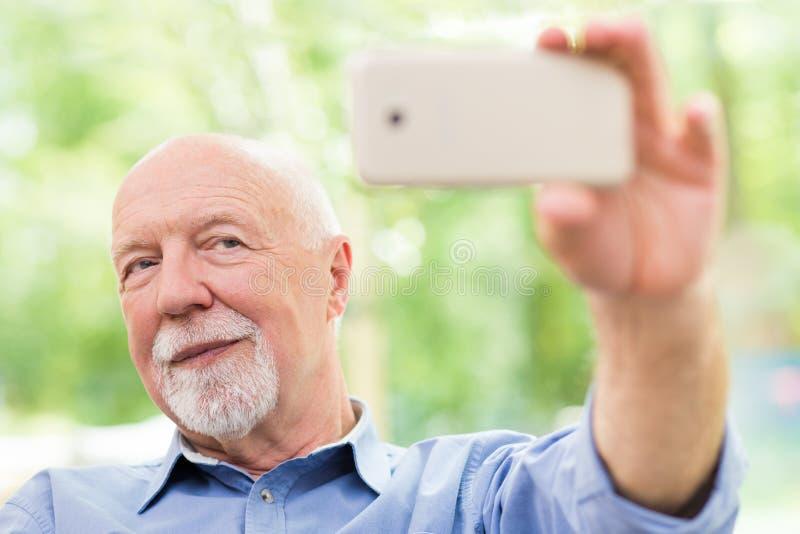 Takin adulto del hombre un selfie con un teléfono fotos de archivo libres de regalías