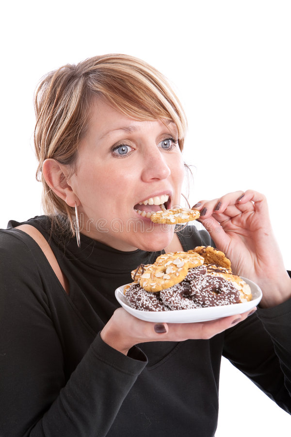 Taking a bite. Pretty blond girl taking a bite out of a cookie royalty free stock photos