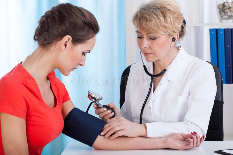 Taking blood pressure of female patient stock photos
