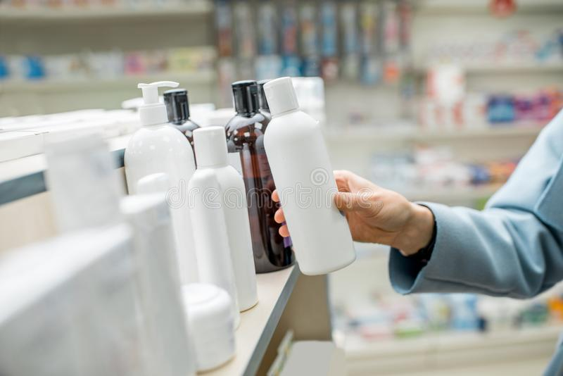 Taking a bottle with cosmetics in te pharmacy stock photos