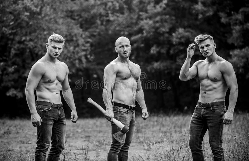 Taking break. brutal guys pose with naked torso. handsome guys with sexy body. Sports and leisure. mesomorph. three. Muscular men with axe. athletic men use ax royalty free stock photography