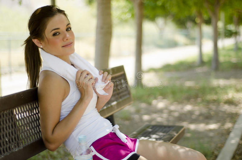 Taking a break after exercising. Beautiful woman resting on a park bench after running royalty free stock images