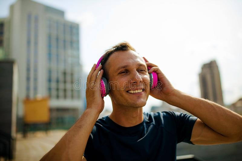 Taking a break. joyful mature gentleman in casual smiling while listening to music playing in his headphones. Close up of attractive young man relaxing after royalty free stock photography