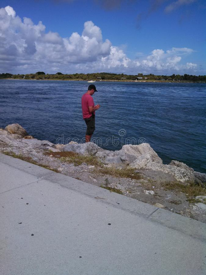 Taking A Break. Man looking at phone at waters edge stock photos