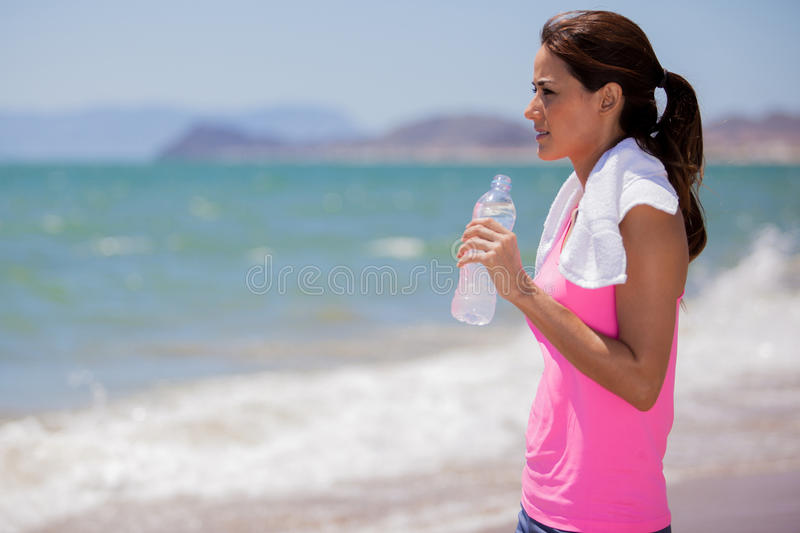 Taking a break from running. Beautiful young woman taking a water break from running while looking at the ocean royalty free stock photos