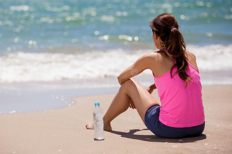 Taking a break from running. Young woman in sporty outfit taking a break to drink water after running at the beach stock images