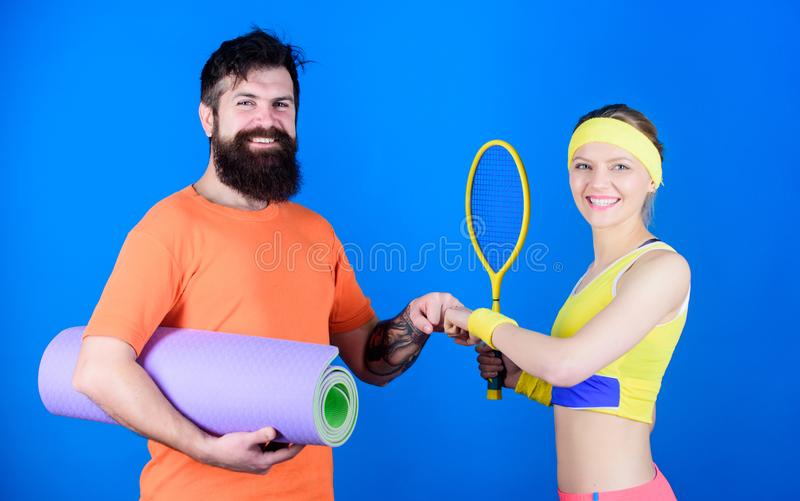 Taking a break. Sporty couple training with fitness mat and tennis racket. Strong muscles and body. Happy woman and. Taking a break. Sporty couple training with royalty free stock images