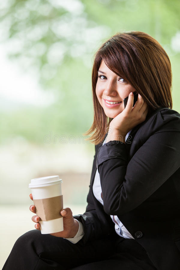 Taking a call on a coffee break. Pretty business woman talking on her cell phone while relaxing on a coffee break stock image