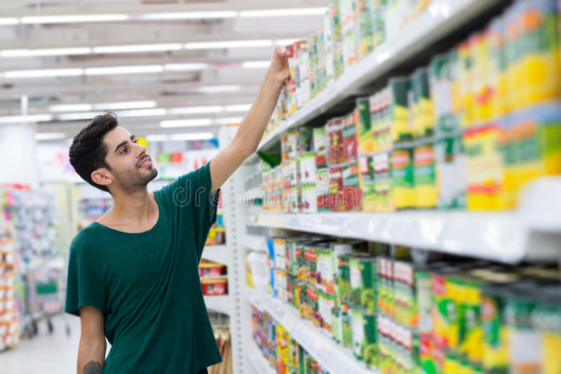 Taking canned food. Young customer taking canned food from the shelf in the store stock images