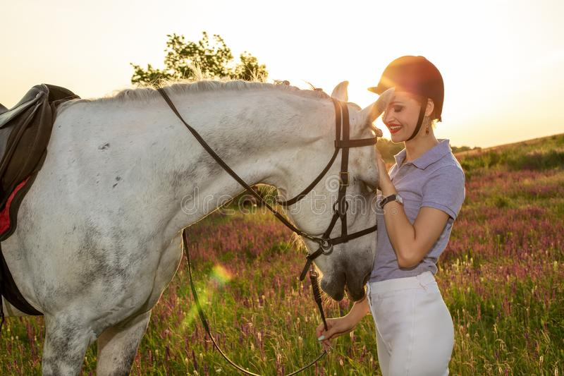 Jockey young girl petting and hugging white horse in evening sunset. Sun flare. Taking care of animals, love and friendship concept. Jockey young girl petting stock photography