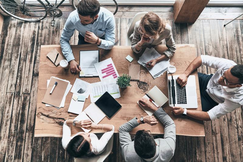 Taking care of business. Top view of young modern people in smart casual wear working while sitting in the office stock photos