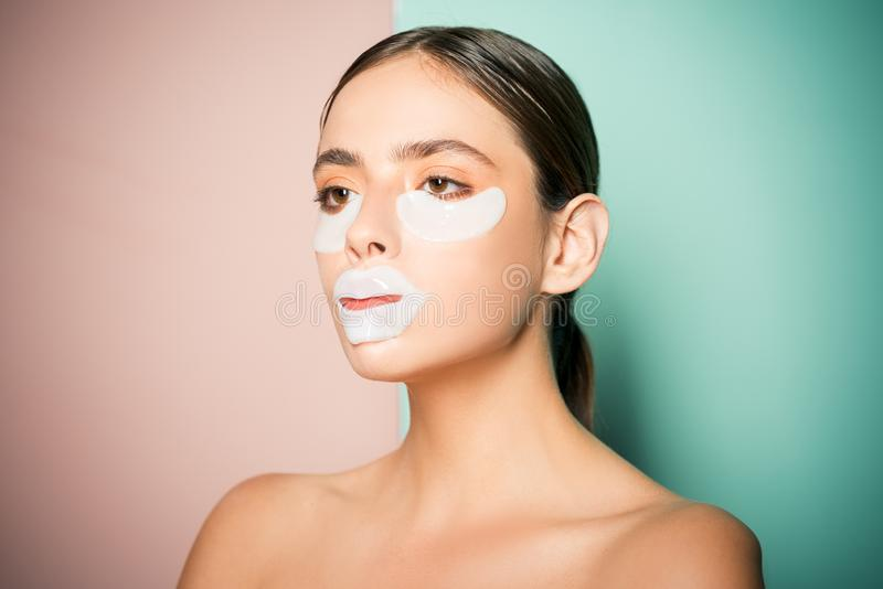 Taking care of her skin. Pretty woman using eye patches spending time at home. Daily pampering routine. Modern cosmetics royalty free stock photo