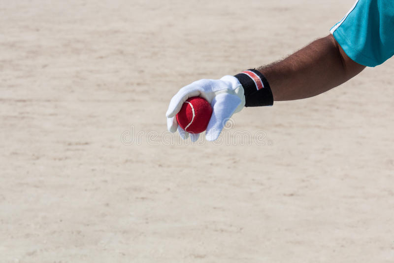 Taking the catch of red ball with hands. Wearing white gloves in open sandy ground stock images