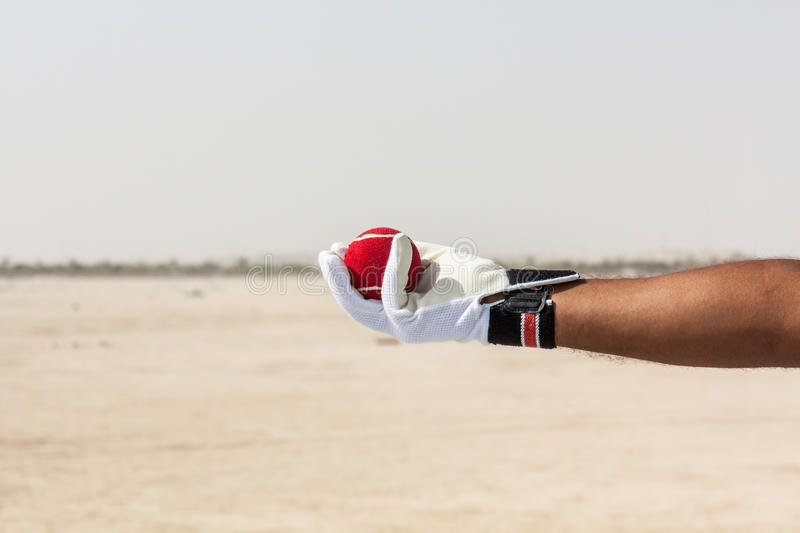 Taking the catch of red ball with hands. Wearing white gloves in open sandy ground stock photography