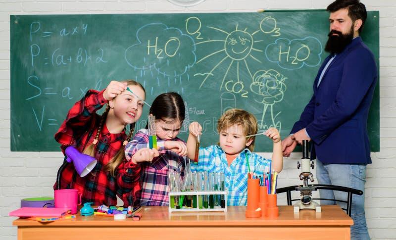 Taking closer look. chemistry lab. back to school. happy children teacher. kids in lab coat learning chemistry in school stock photo