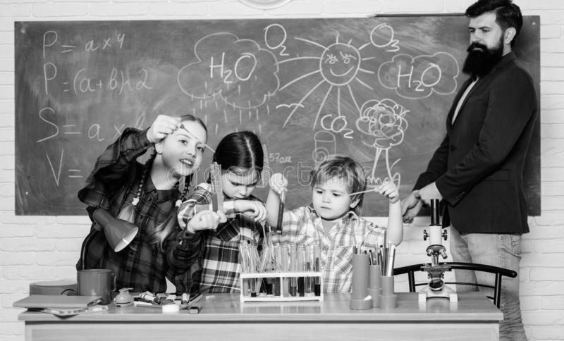 Taking closer look. chemistry lab. back to school. happy children teacher. kids in lab coat learning chemistry in school. Laboratory. making experiment in lab royalty free stock photography