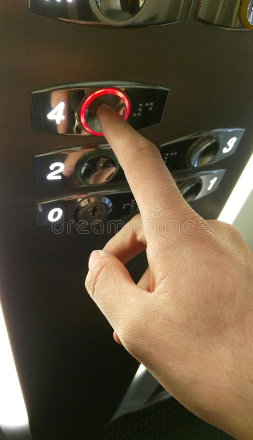 Young man pressing button in elevator, hand close up. Caucasian man hand close up taking the lift in a building, going upstairs royalty free stock image