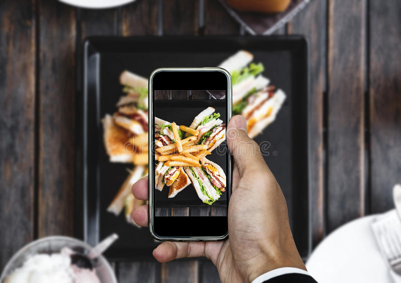 Taking food photo, food photography by smart phone, club sandwich with french fries on wooden table stock photography