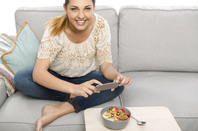 Taking foodie photos before eatting. Woman sitting on the couch ready to eat and talking picture to her food stock photo
