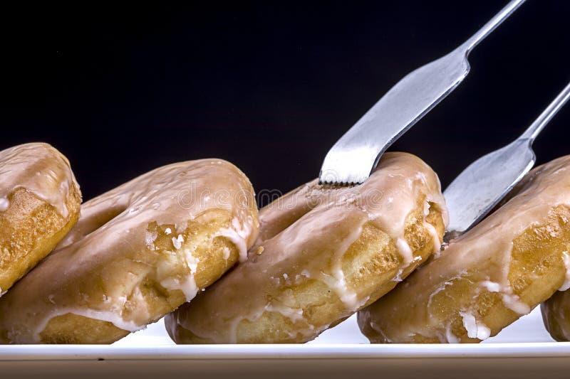 Taking a glased doughnut. A macro photo of tongs reaching for fresh glazed doughnuts stock photos